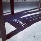 La sombra proyectada en la calle de un banco con la palabra Getafe, instantánea de Jorge Martín